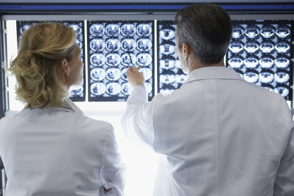 A male and female doctor discussing about the x-ray image