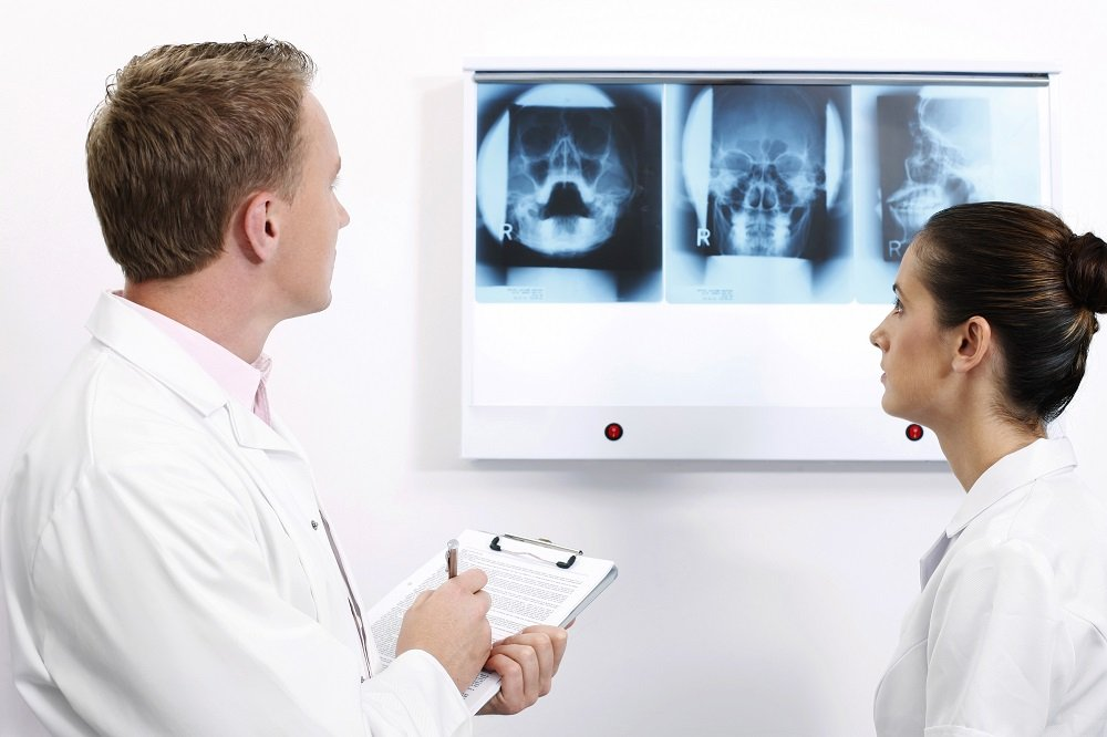 Male and Female dentist looking to a x-ray image of tooth