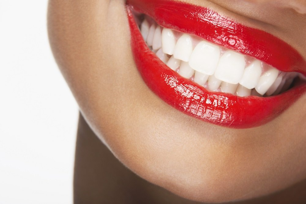 close up mouth with a red lipstick and a beautiful white teeth with a smile