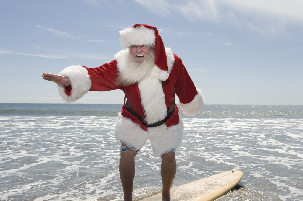 Man at the beach wearing Santa Claus costume while on top of the surfing board