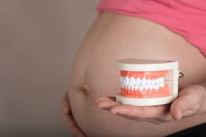 A pregnant womans belly and a hand holding teeth
