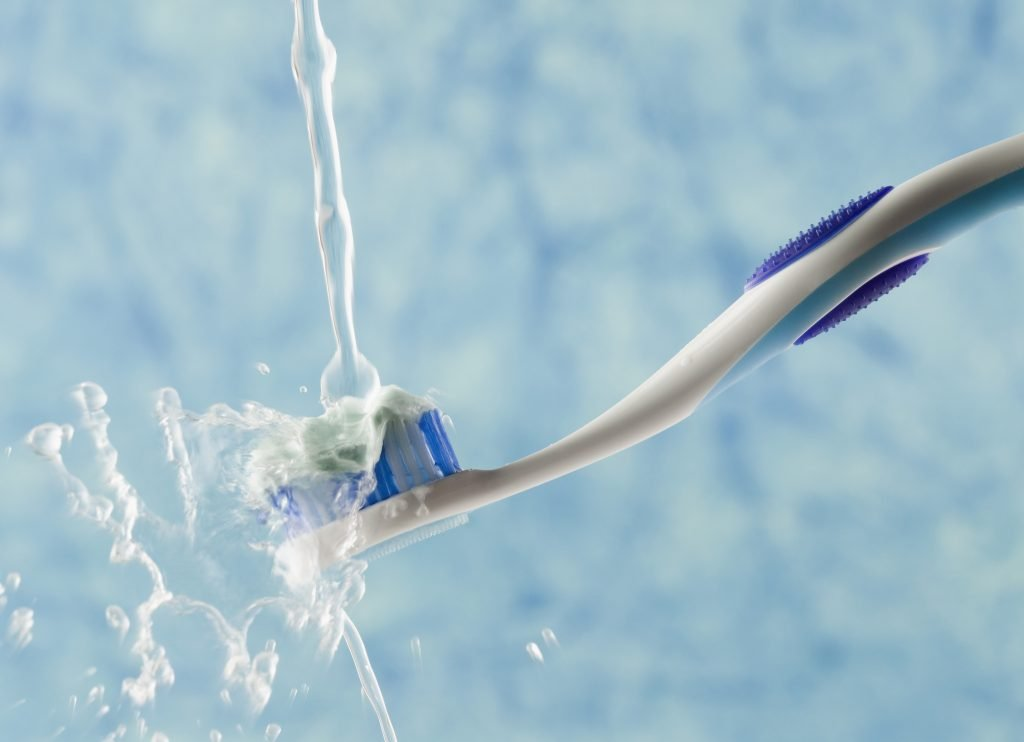 Toothbrush underneath water flowing from a tap